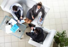 above angle of three business partners discussing documents - stock photo