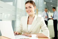 a beautiful businesswoman looking at camera with working men on background - stock photo