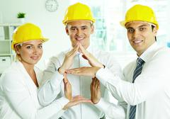 A group of smiling architects in helmets showing hand sign of house Stock Photos
