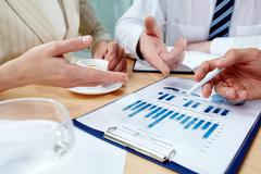image of human hands pointing at business document at meeting - stock photo