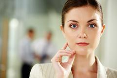 serious businesswoman looking at camera with calm expression - stock photo