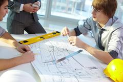 Young architect discussing new project with colleague in office Stock Photos