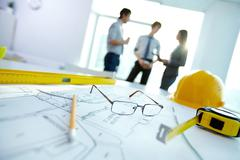 image of engineering objects on workplace with three partners interacting on bac - stock photo