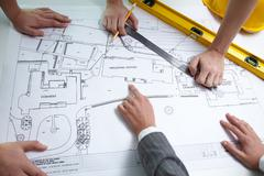 hands of constructors over architectural project - stock photo