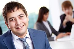 successful businessman looking at camera with working colleagues on background - stock photo