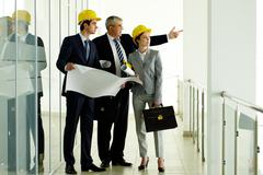Stock Photo of three architects standing in office building and interacting