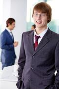 successful businessman looking at camera with colleagues on background - stock photo
