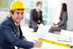 Young engineer looking at camera with his colleagues on background Stock Photos