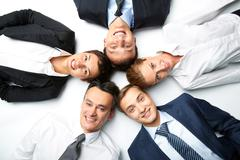 five business people lying on the floor, looking at camera and smiling - stock photo