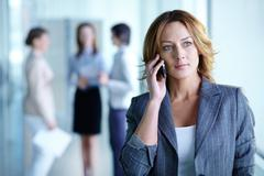 Image of pretty businesswoman calling on the phone in working environment Stock Photos