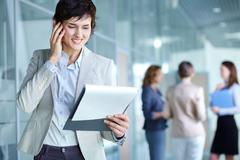 image of busy female calling on the phone and reading document in working enviro - stock photo