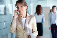 Image of agent with paper speaking on the phone in working environment Stock Photos
