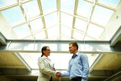 Business people shaking hands concluding a deal or greeting each other Stock Photos