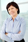 Mature businesswoman looking at camera with smile Stock Photos