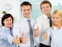 Ryhmä onnistuneen liikemiesten osoittaa thimbs ylös ja katsot kameraa Kuvituskuvat