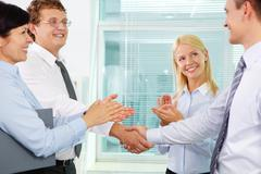 Successful businessmen handshaking while two females applauding after signing ne Stock Photos