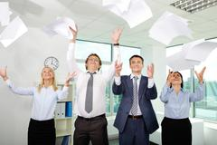 group of excited businesspeople throwing papers in office - stock photo