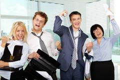 Group of tired businesspeople showing gladness after making excellent deal Stock Photos