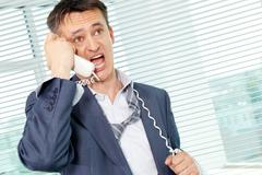 sloppy businessman shouting into phone receiver in office - stock photo