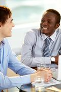 Image of two confident business partners interacting at meeting Stock Photos