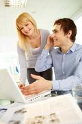 Image of happy man speaking on the phone while his secretary looking at laptop n Stock Photos