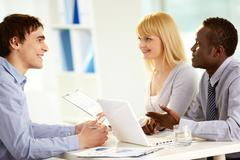 Image of three confident business partners interacting at meeting Stock Photos