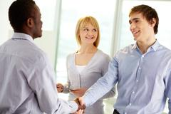 Image of confident business partners handshaking at meeting Stock Photos