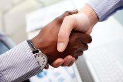 Stock Photo of close-up of businessmen shaking hands, caucasian and african-american