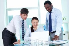 three colleagues working with laptop at meeting - stock photo