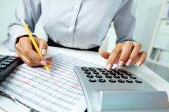 Photo of hands making notes with pencil and pressing calculator buttons Stock Photos