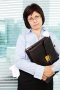 Sloppy businesswoman with briefcase looking at camera Stock Photos