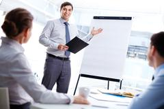 Smiling business man presenting his new strategy to the colleagues Stock Photos