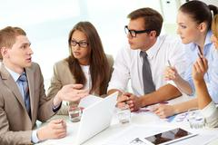 image of confident partners listening to young businessman at meeting - stock photo