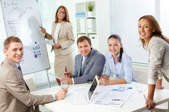 Image of confident partners looking at camera during presentation Stock Photos