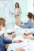 happy top manager standing by the whiteboard and interacting with business partn - stock photo