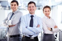 elegant business team standing cross-armed expressing positivity and strong infl - stock photo