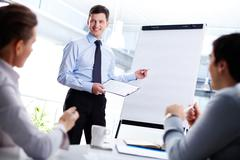 Cheerful office worker pointing at the blank whiteboard making a presentation Stock Photos