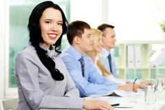 Young business people taking part in seminar, lovely girl being in the foregroun Stock Photos
