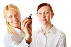 young business woman writing with a marker, her colleague looking closely - stock photo