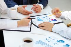 close-up of business group analyzing financial papers for the certain period - stock photo