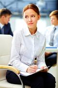 Pretty business woman with dreamy look making notes white at office Stock Photos
