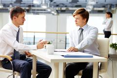 male business people of different age having a serious conversation - stock photo