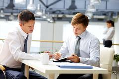 Senior businessman helping his younger colleague with financial analysis Stock Photos