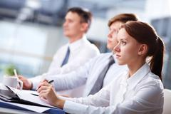 Row of business people attending a seminar and listening closely Stock Photos