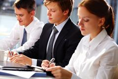 dedicated business team writing down important information at seminar - stock photo