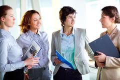 group of business ladies discussing latest business news - stock photo