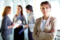 Portrait of a mature business lady standing in the foreground, her female collea Stock Photos