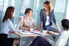 pretty females discussing business matters in the boardroom - stock photo