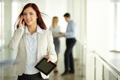 Business lady answering the phone with a smile with working team on background Stock Photos