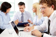 Stock Photo of young man working on the laptop, his colleagues holding a discussion in the back